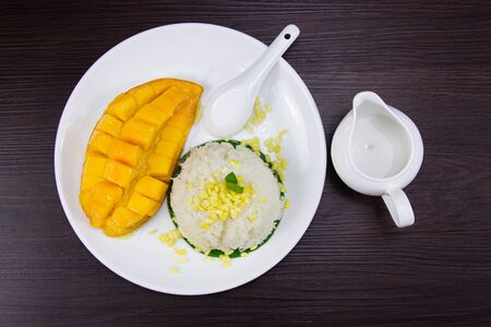 Sticky rice with fresh ripe mango with coconut milk put white plate on brown dark wooden table. Top view.