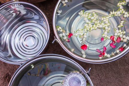 Jasmines and rose petals floating in large stainless bucket for songkran festival in thailand.