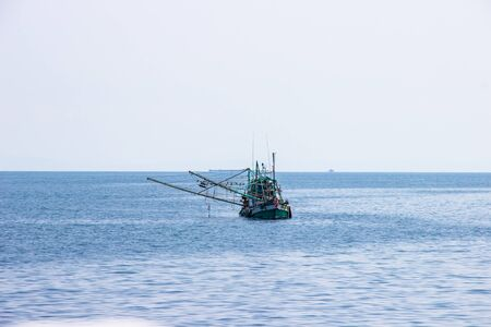 Traditional green thai fishing boat floating in the bay of thailand near koh chang on day the bright sky.