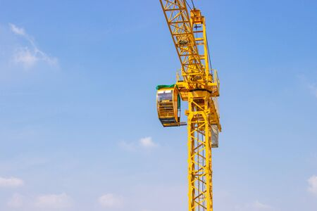 Yellow crane is used in the construction of high buildings for tool of large industry under the blue sky and white clouds. Standard-Bild