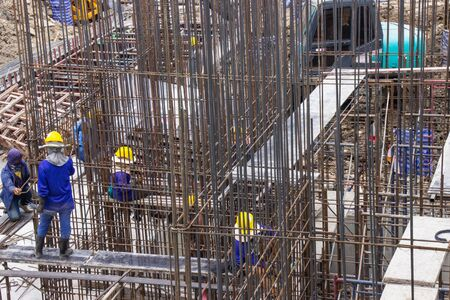 Construction workers fabricating large steel bar reinforcement bar at the in construction area building site.