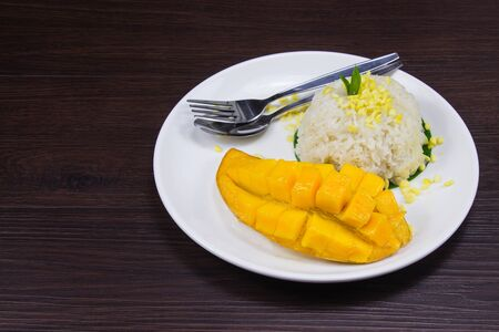 Sticky rice with fresh ripe mango with coconut milk put white plate on brown dark wooden table is thai style tropical dessert.