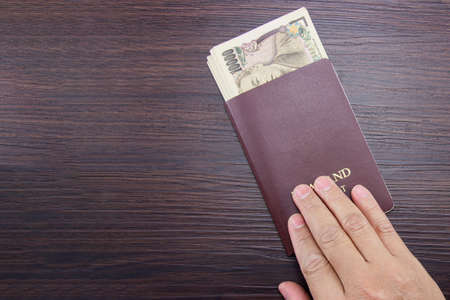 Man's hand holding international passport and Japanese money on brown dark wooden table.