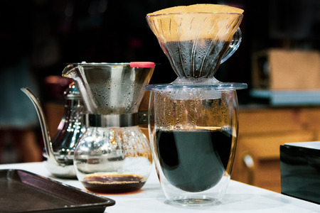 Drip coffee brewing, Barista pouring water on coffee ground with filter
