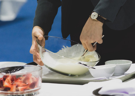 Hands preparing cream, chef whisking cream in kitchen
