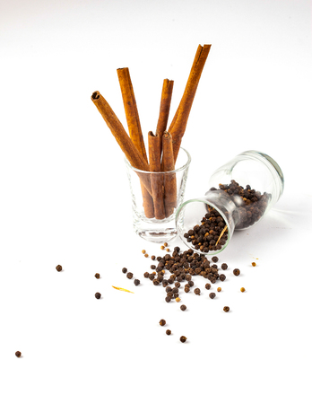 cinnamon and black pepper seeds in a glass, Black pepper is scattered on a white background from glass bottle Imagens