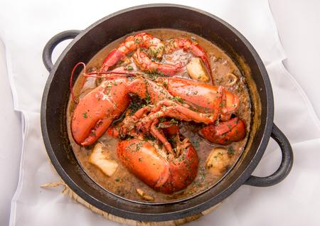 Riz paella espagnol traditionnel avec du homard et de la viande sur la poêle