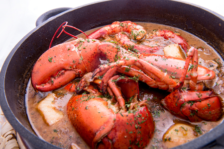 Traditional spanish paella rice with lobster and meat on pan