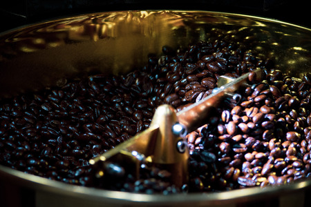 Roasted coffee in coffee roaster, Machine for roasting coffee close up, bean roasting
