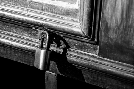 Old lock on a wooden door with rusty closed padlock, Vintage Black and white photo