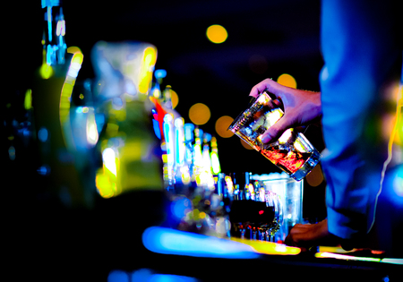 Bartender making alcohol cocktail at bar counter at nightclub, barman is making cocktail Stock Photo