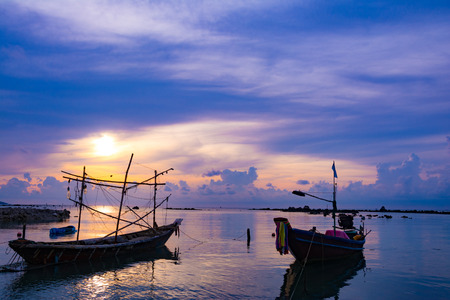 Fishing boat in the sea, sunset and silhouettes of wooden boats