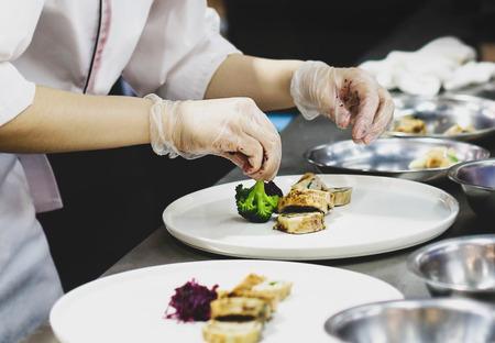 Szef kuchni przygotowujący jedzenie, posiłek, w kuchni, gotowanie szefa kuchni, szef kuchni dekorujący danie, zbliżenie Zdjęcie Seryjne