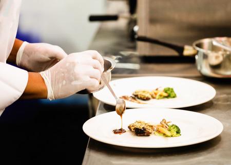 Chef che prepara cibo, pasto, in cucina, chef che cucina, chef che decora piatto, primo piano