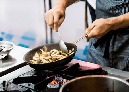 Chef frying mushrooms in the kitchen of the restaurant