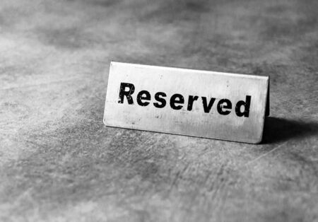 Reserved table sign in restaurant, silver reserved plate, black and white