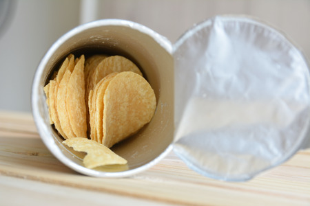 Slice potato chips in can on wood table