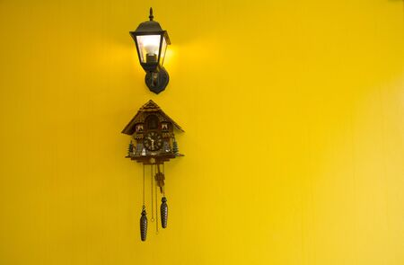 Wall clock with lamp On a yellow background