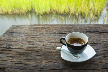 Black coffee mug on wooden floor and green meadow background Stock Photo