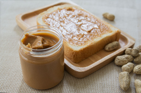 Peanut butter sandwich or toast on wooden plate with peanut shell