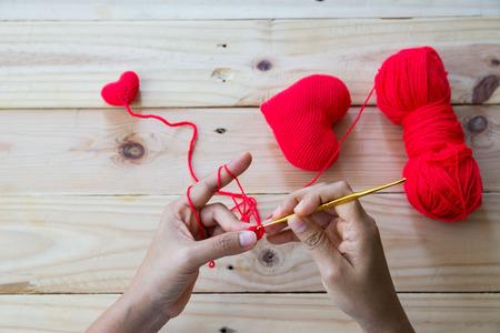 Handmade crochet red heart on wood background flat layout Banco de Imagens