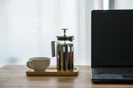 French press with laptop computer on table