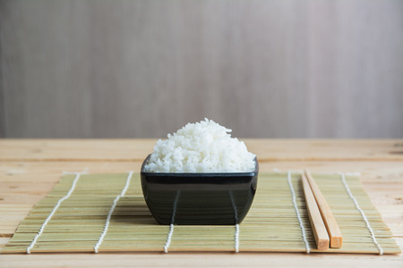 Jasmine rice in white cup On a bamboo mat