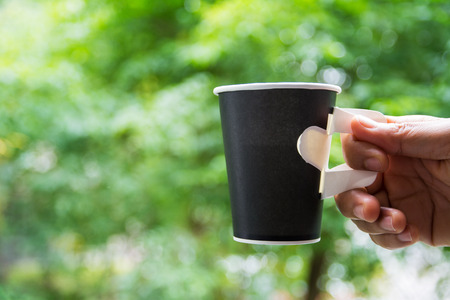 Black paper coffee cup in hand on green leave background