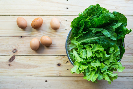 Green leafy vegetables with eggs on wooden background Stock Photo