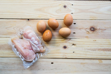 Green leafy vegetables with eggs and fresh chicken on wooden background