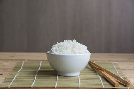 Arroz jazmín en taza blanca sobre una estera de bambú