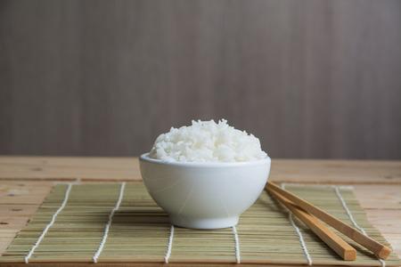 Riz au jasmin dans une tasse blanche sur une natte de bambou