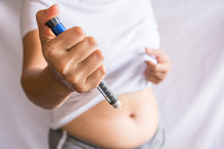 Diabetes concept insulin syringe injection shot into abdomen
