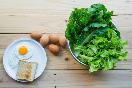 Green leafy vegetables with eggs and bread on wooden background