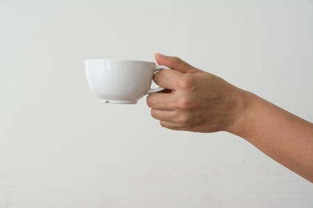Hand holding a white cup on white background