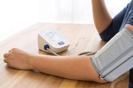 Women measures her blood pressure and heart rate with digital pressure gauge