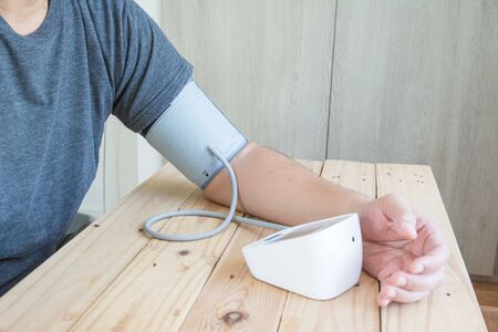 Men measures  blood pressure and heart rate with digital pressure gauge Reklamní fotografie