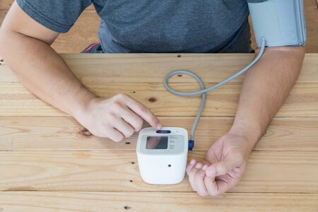 Men measures  blood pressure and heart rate with digital pressure gauge Stock fotó