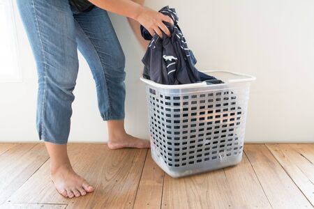 Women with laundry basket on floor and white background