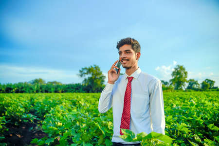 young indian handsome agronomist talking on smartphone at field Stok Fotoğraf