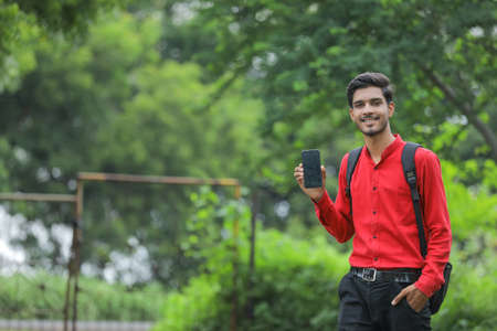 Young indian college student showing smart phone over nature background