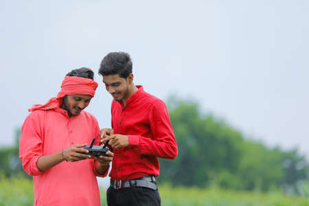 Indian farmer and agronomist using drone at agriculture field