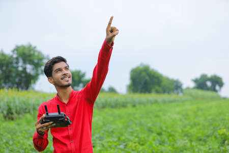 Indian agronomist seeing of flying drone in sky at agriculture field