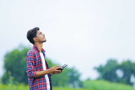 Young indian agronomist operate or control of flying drone at agriculture field