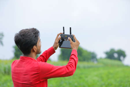 Remote control holding in hand over agriculture background