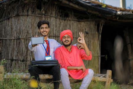 Young indian bank officer showing mobile screen with farmer