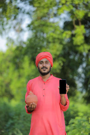 Young indian farmer holding clay piggy bank and showing smart phone in hand