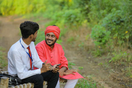 Young indian banker discuss with farmer at field