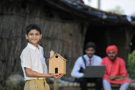 Dream home concept : poor farmer little child holding handmade home in hand