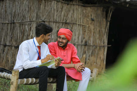 Young indian banker discuss with farmer at home